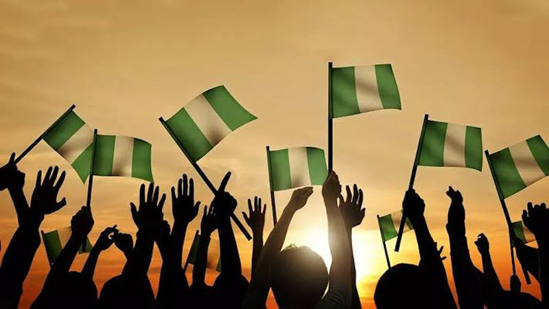 A cheering crowd bearing Nigeria flags