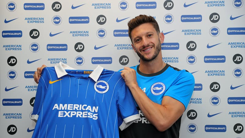 Adam poses with Brighton's Jersey after signing for the club