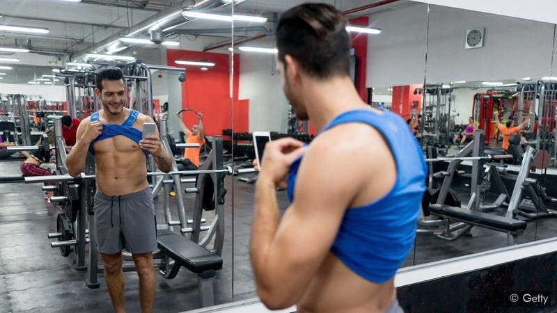 A young man taking a picture showing his six-packs at the gym