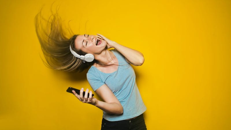 A woman with a headphone listening to music