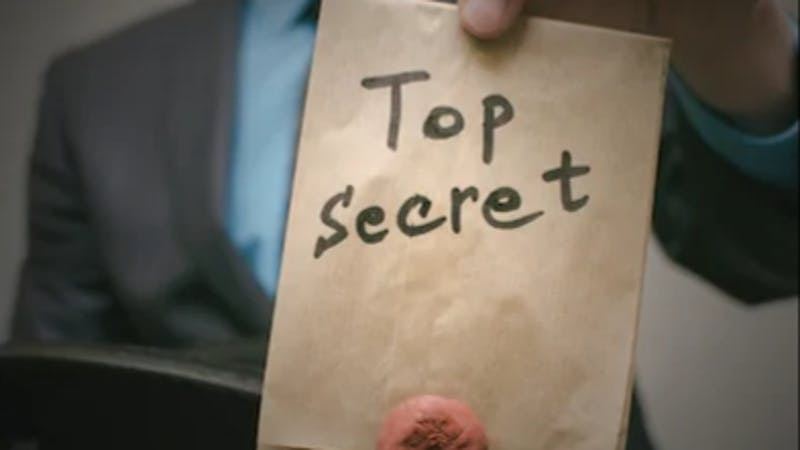 "A man holding up a file tagged, ""top secret"""