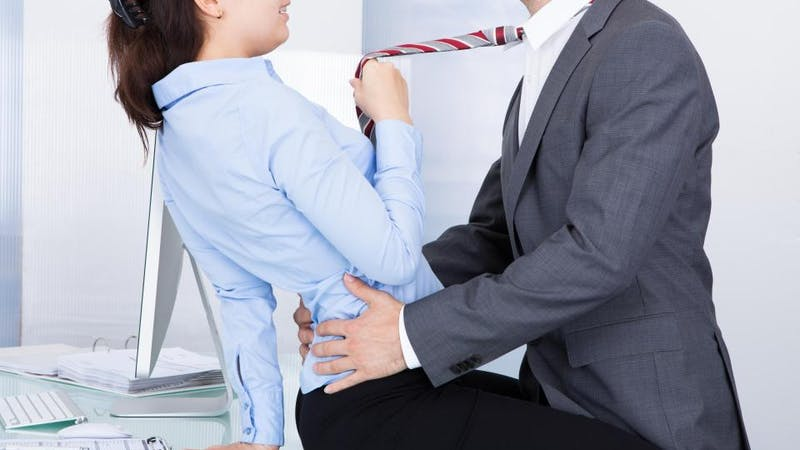 A lady in a sexual position with a man in the office