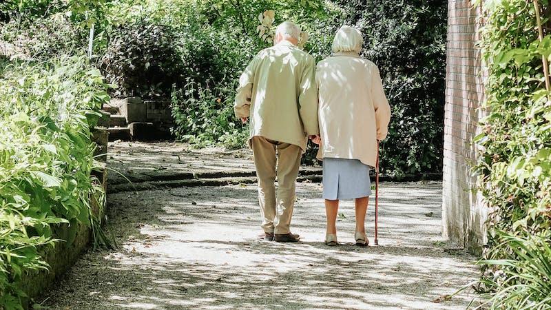 An elderly couple walking in a park.