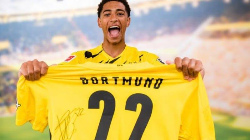 Jude Bellingham holding the number 22 shirt after signing for Dortmund