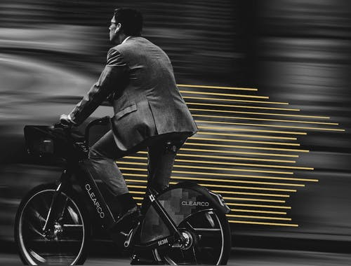 A man in a suit bikes in front of a blurred background with golden lines trailing behind him