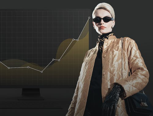 A woman stands in front of a chart showing upward growth.