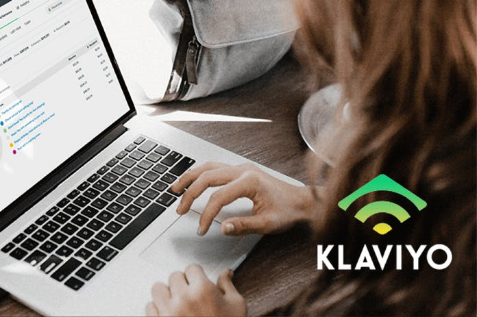 Person typing on a laptop with a Klaviyo logo in the corner
