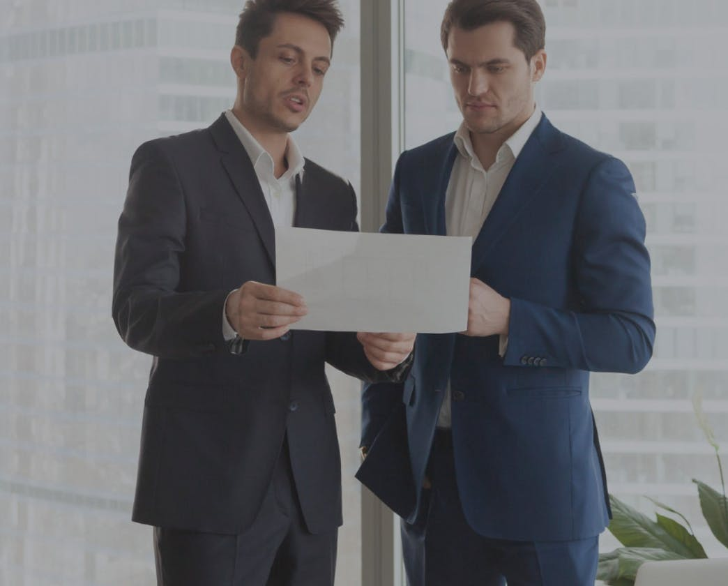 men in suits looking at document