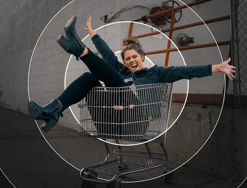 A woman cheers and kicks her leg up while sitting in a shopping cart