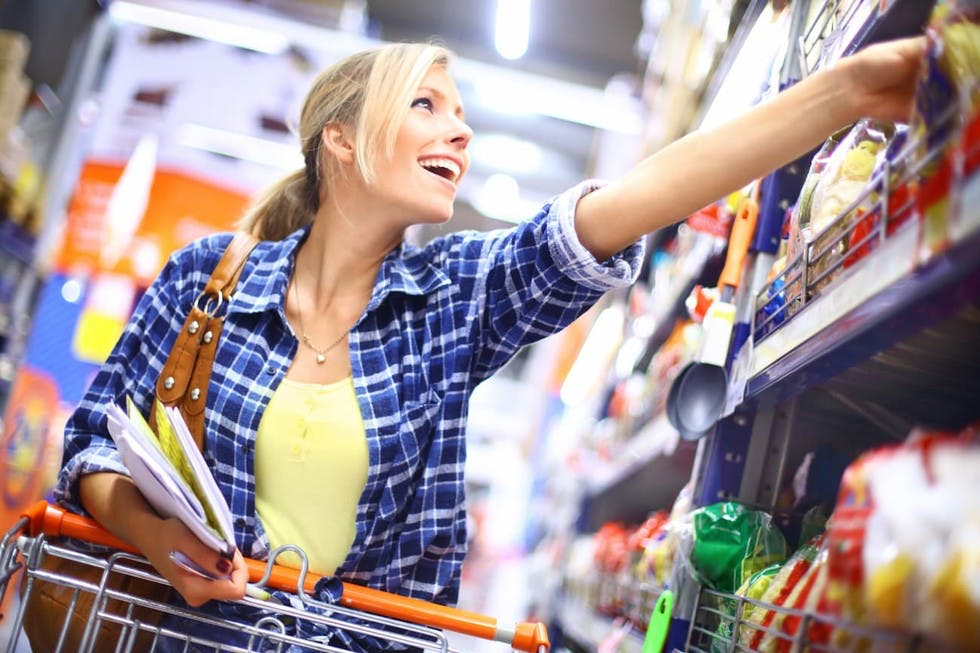 Woman reaching for store items while listening to Cloud Cover Music