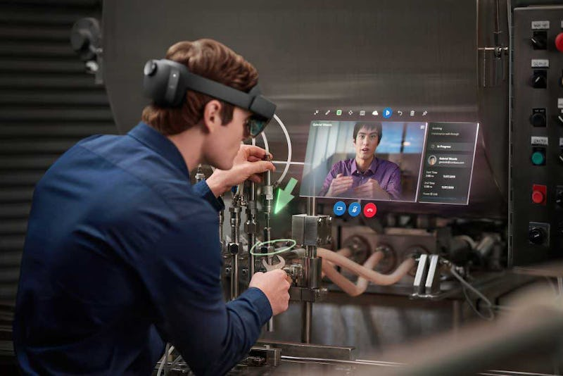 Worker wearing a Microsoft HoloLens fixing a machiine as they are walk through a expert with Remote Assist