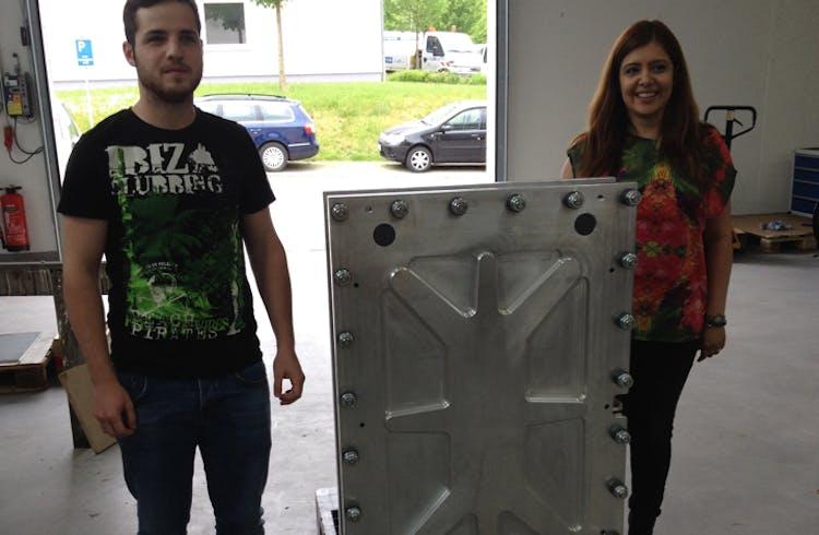 Zwei CMBlu-Mitarbeiter stehen neben einem Stack aus Metall.
