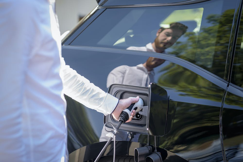 Young driver quick-charging an electric vehicle for a fast, smooth consumer experience.