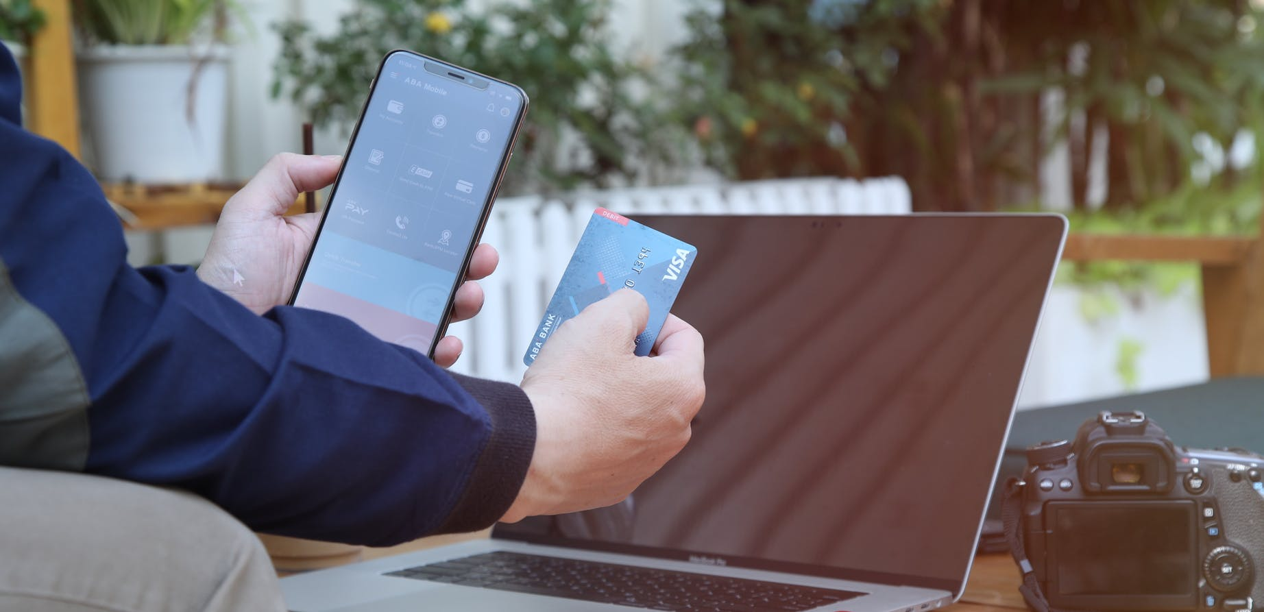 Man holding phone and credit card in front of laptop