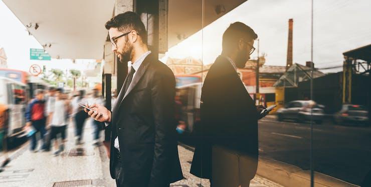 Homem em pé na rua mexendo no celular