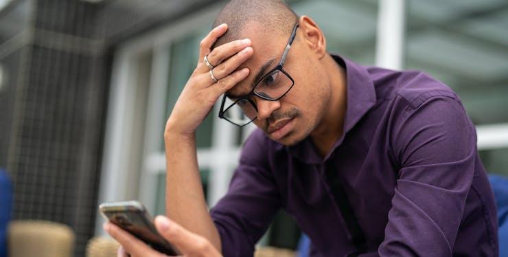 Homem irritado olhando para o celular sem sinal