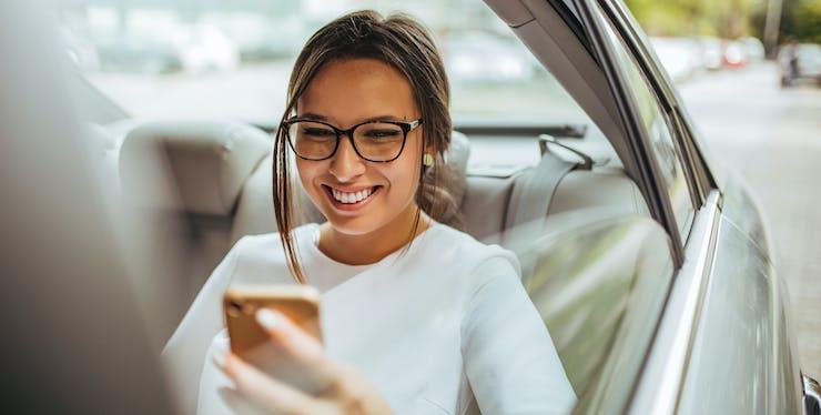 Mulher mexendo no celular dentro do carro