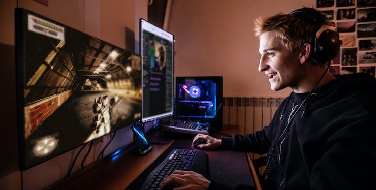 Jovem se divertindo enquanto joga online no computador