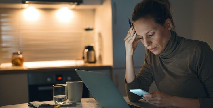 Mulher séria em frente ao computador enquanto mexe no celular