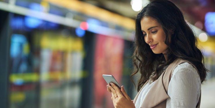Mulher mexendo no celular no metrô