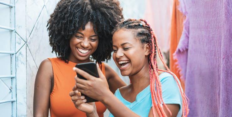 Duas mulheres sorrindo enquanto usam o celular
