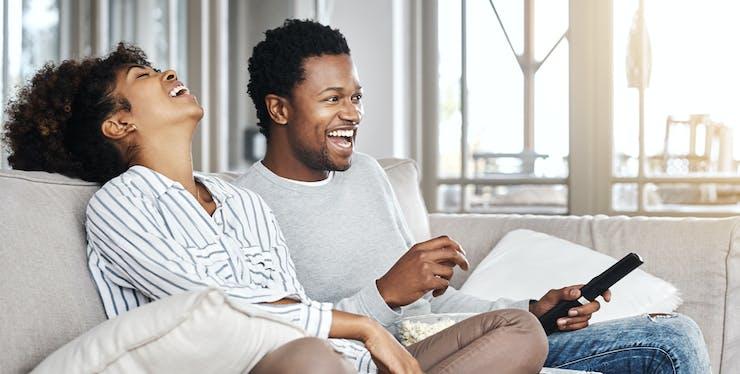 Casal sorrindo enquanto assistem TV