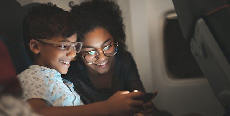 Mãe e filho olhando para a tela de celular com internet fibra ótica