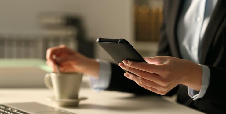 Mulher segurando o celular enquanto toma café