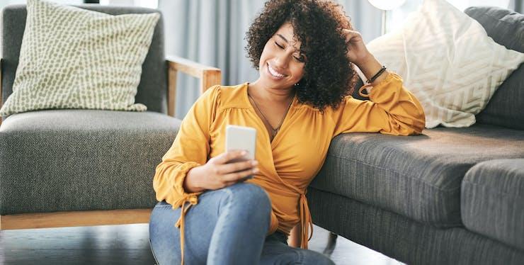 Mulher sentada no chão mexendo no celular