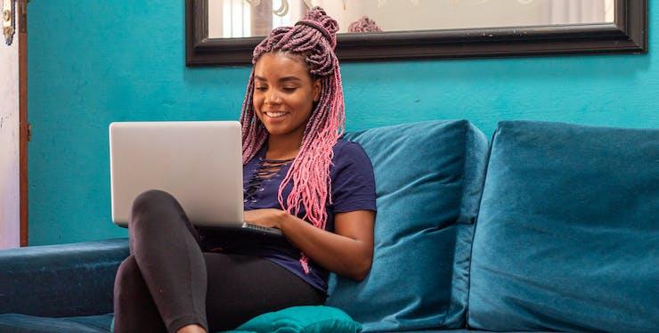 Mulher sentada ao sofá com um notebook no colo