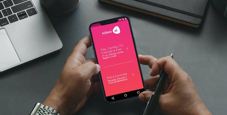 Pessoa com celular na mão na tela principal do app Minha Oi