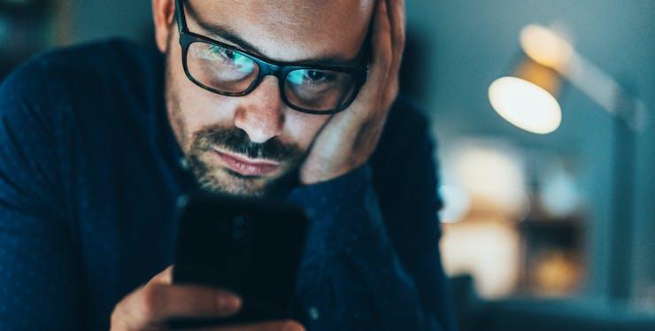 Homem irritado enquanto olha para o celular
