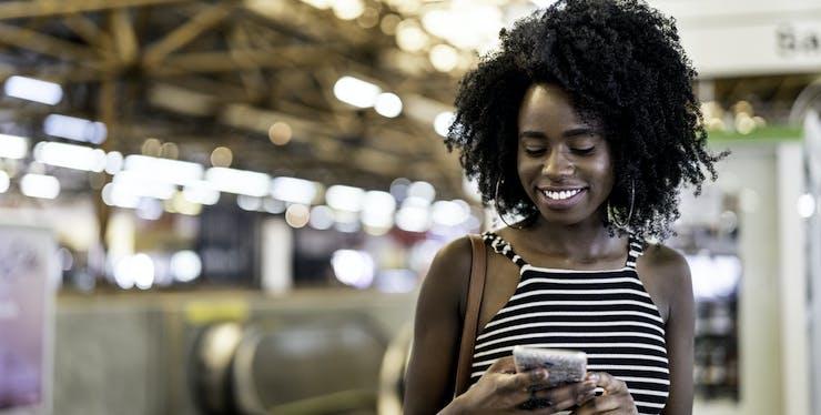 Mulher sorri enquanto usa o celular na rua