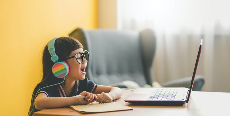 Menina contente enquanto usa o computador