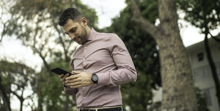Homem usando o celular para saber o número da Claro