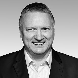Ein lächelnder Mann mit weißem Hemd und schwarzem Sakko.