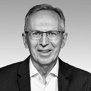 Ein lächelnder Mann mit Brille, weißem Hemd und schwarzem Sakko.