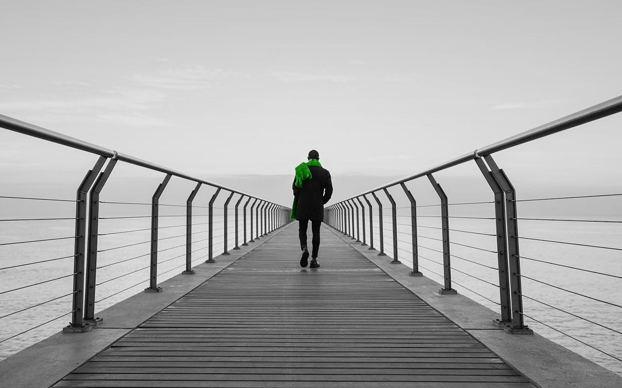 Ein Mann in schwarzem Anzug und grünen Schal, der einen Steg entlang läuft.