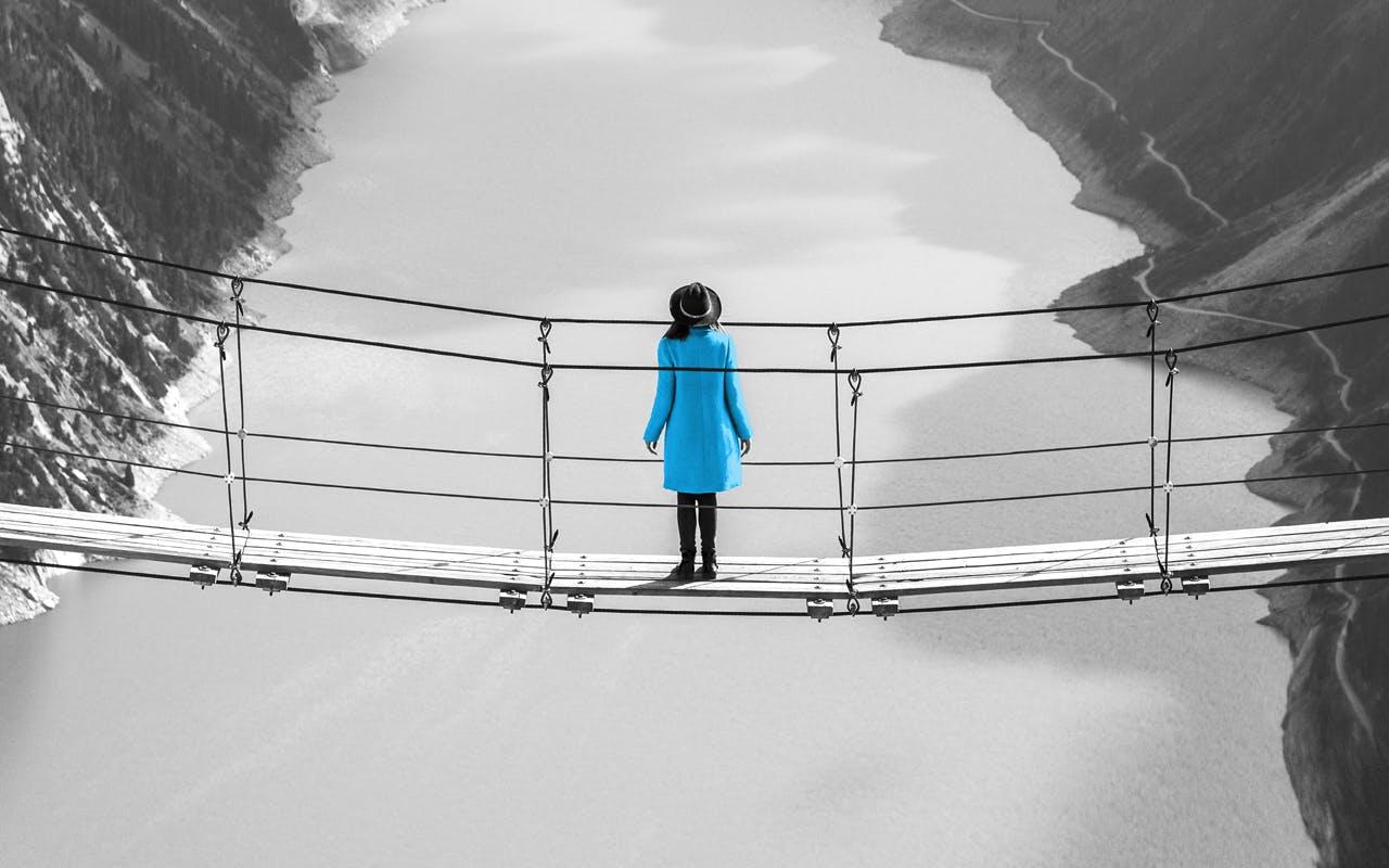 Eine Person die mit einem blauen Mantel und einem schwarzen Hut auf einer Hängebrücke steht.