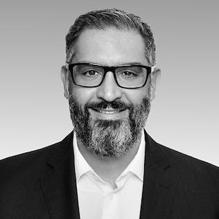 Ein lächelnder Mann mit Brille, Bart und schwarzem Sakko.