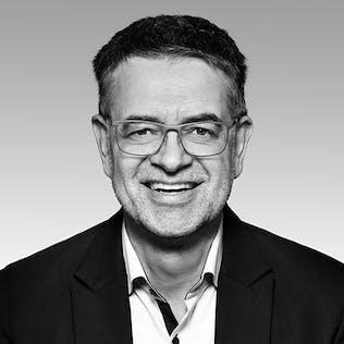 Ein lächelnder Mann mit Brille und schwarzem Sakko.