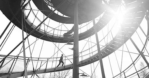 Ein Mensch im schwarzen Anzug, der eine Wendeltreppe hoch läuft.