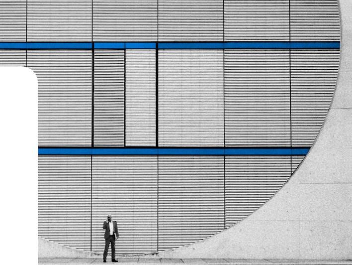 Eine Person im Anzug die an einer blau-grauen Hauswand entlang läuft.