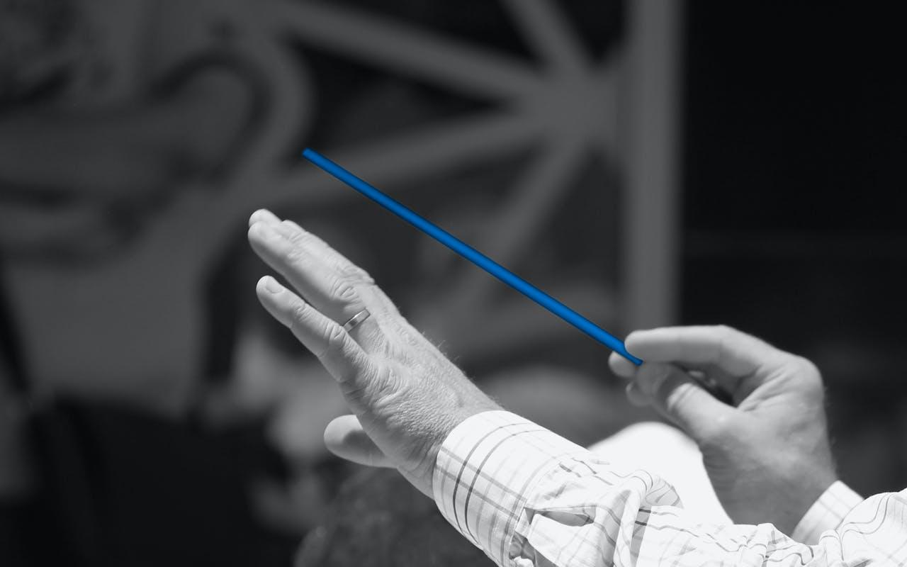 Zwei Hände und die rechte Hand hält einen Dirigentenstab.