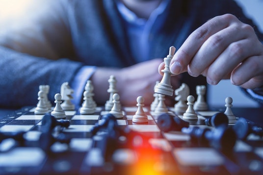Business person playing chess