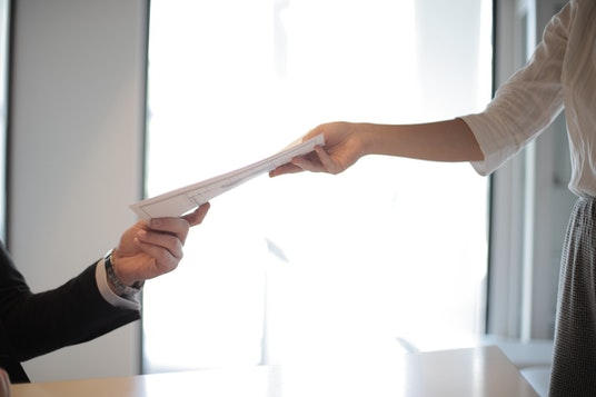 person handing over their resume to employer