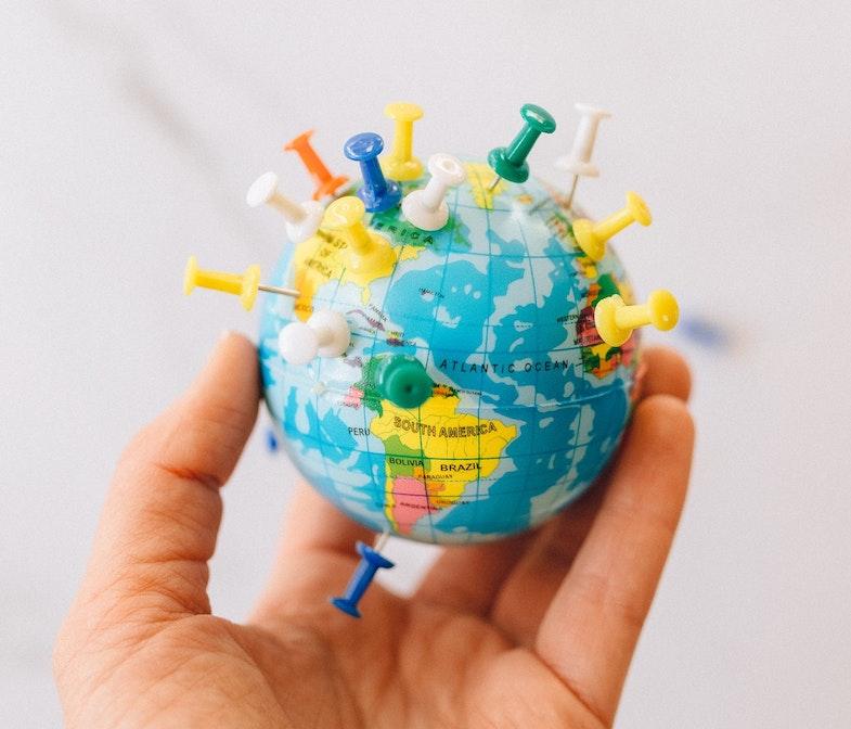 person holding mini globe