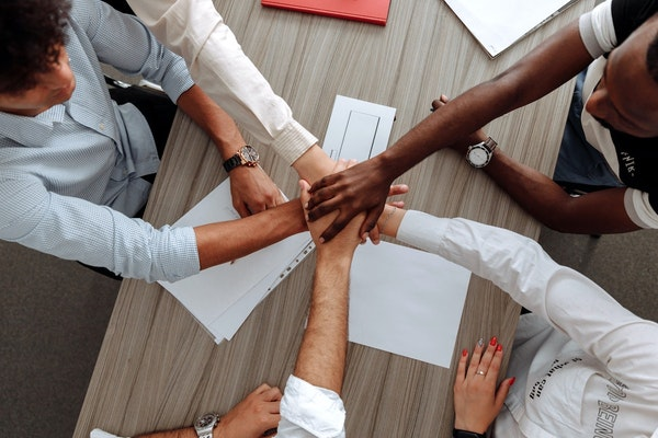 Employees putting hands together for teamwork