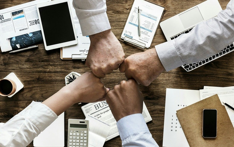 Coworkers hands celebrating around table, data driven investing