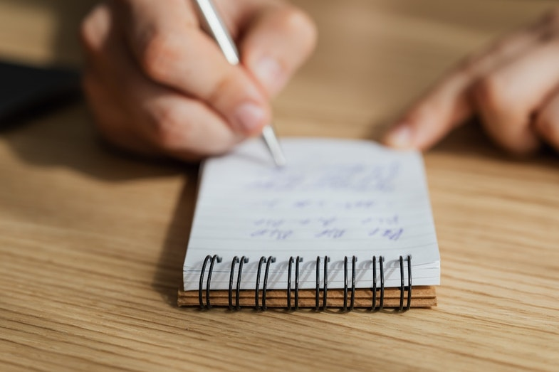 person taking notes on notepad